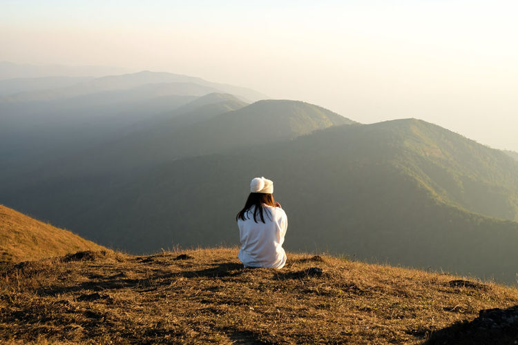 Asia woman sitting on top of mountain