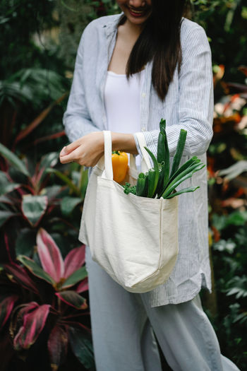 Midsection of woman holding umbrella standing by plants