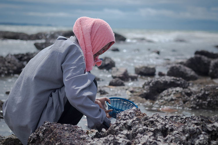 Woman collecting rocks on beach