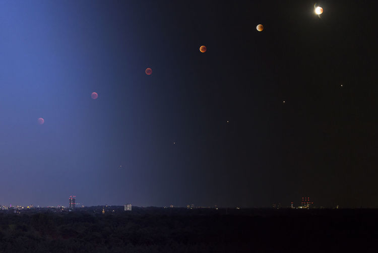 Scenic view of moons over landscape against clear sky at night