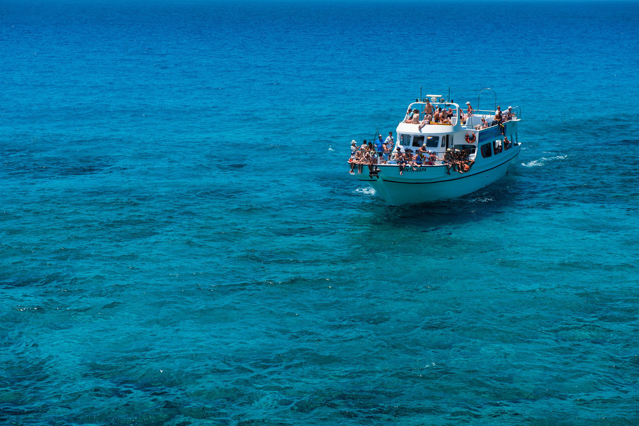nautical vessel, mode of transportation, transportation, sea, blue, water, waterfront, day, sailing, travel, beauty in nature, nature, group of people, real people, outdoors, scenics - nature, rippled, journey, passenger craft, turquoise colored, fishing boat
