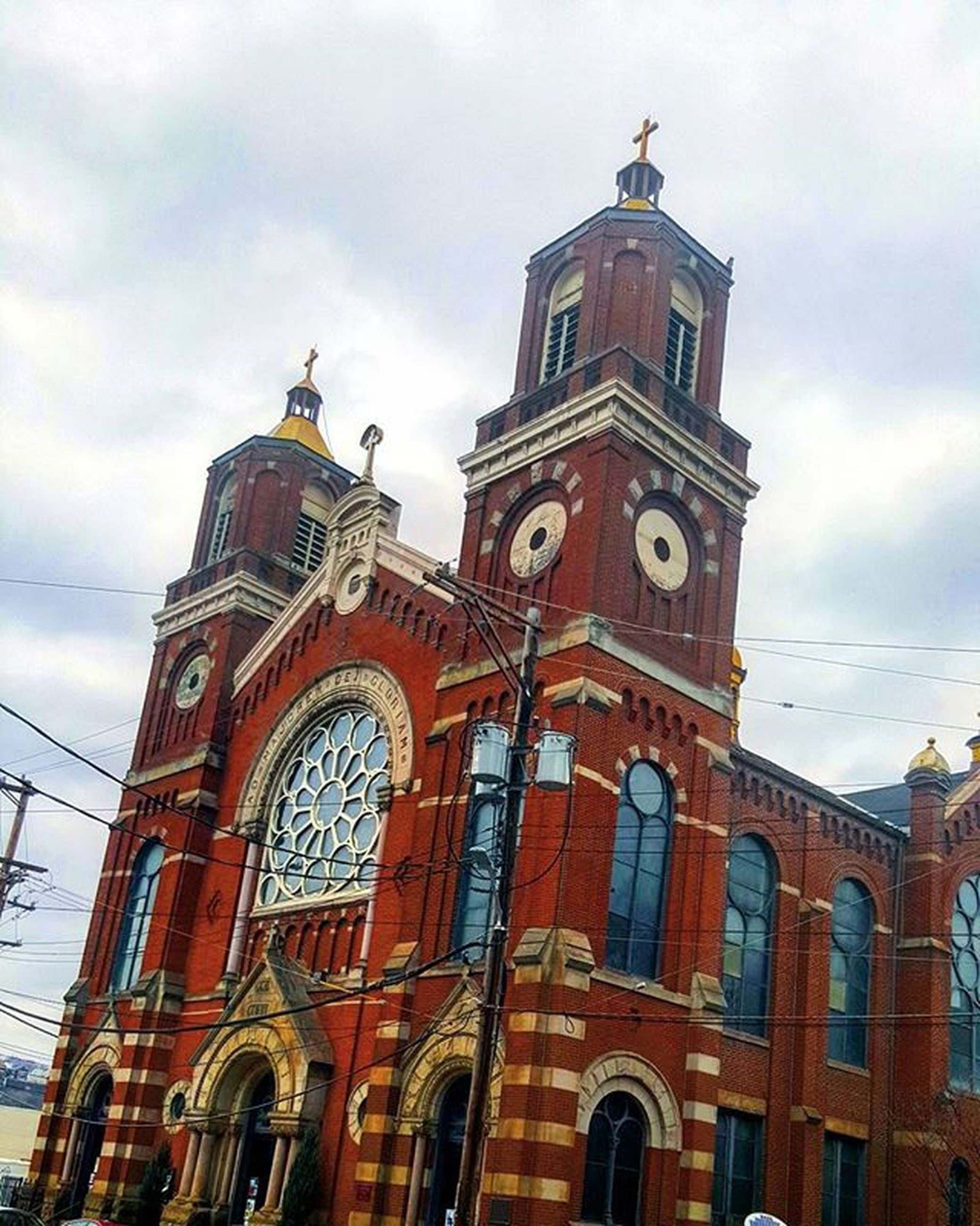 architecture, building exterior, religion, built structure, low angle view, church, place of worship, sky, spirituality, cathedral, cloud - sky, clock tower, tower, travel destinations, cloud, facade, clock, cross