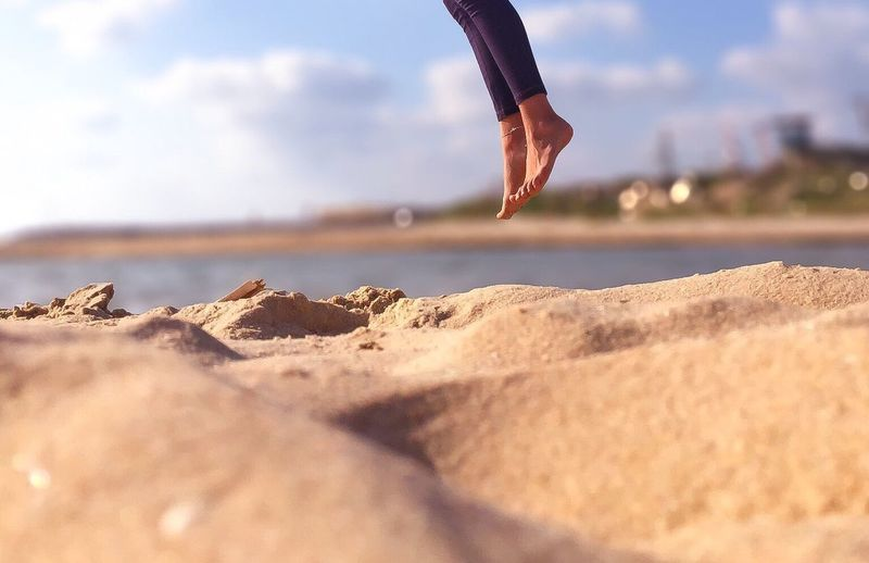 Low section of person jumping on beach against sky