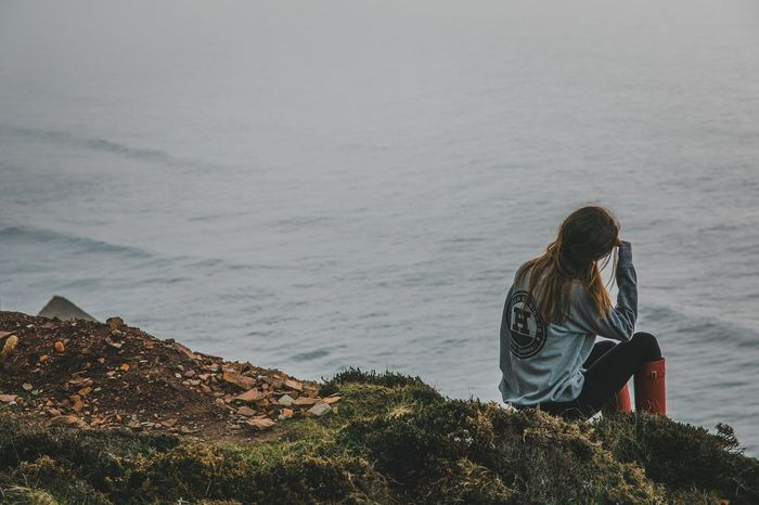Contemplation Beauty In Nature Casual Clothing Day Hairstyle Land Leisure Activity Lifestyles Looking At View Nature One Person Outdoors Real People Rear View Rock Rock - Object Scenics - Nature Sea Sitting Solid Water Women