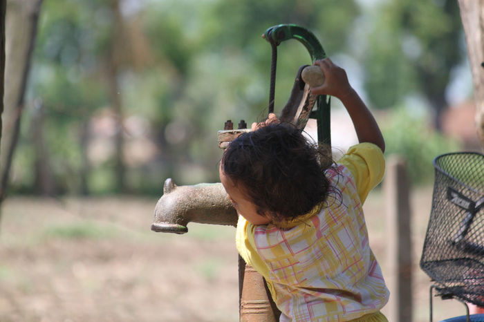 Help Nepal Animal Themes Casual Clothing Childhood Day Focus On Foreground Holding Leisure Activity Lifestyles Nepal Travel One Person Outdoors People Real People Rear View Standing Tree Water Water Pump