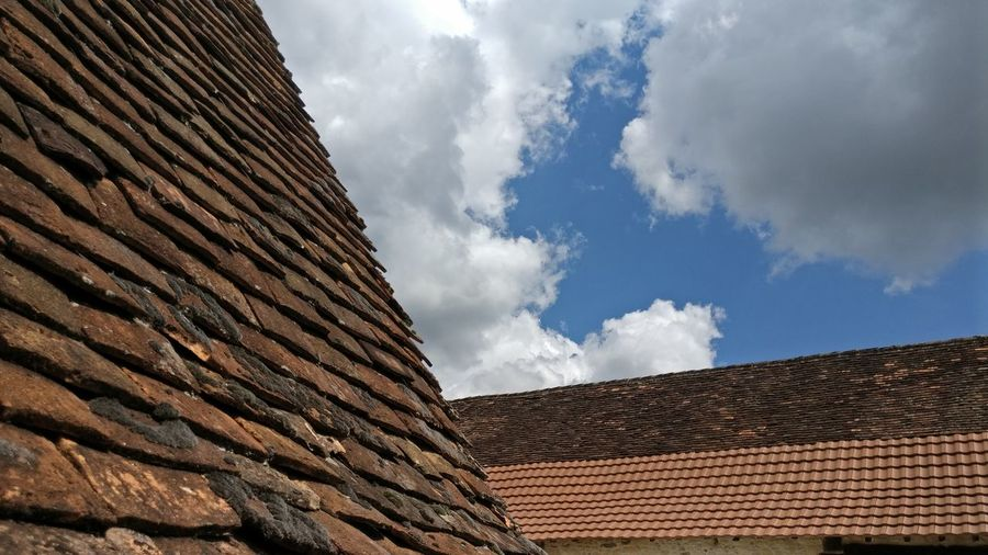 Low Angle View Of Roofs Against Cloudy Sky