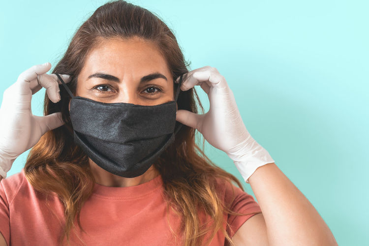 Portrait of young woman covering face against blue background