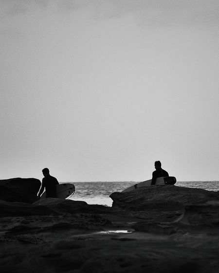 Two men at beach with surfboard