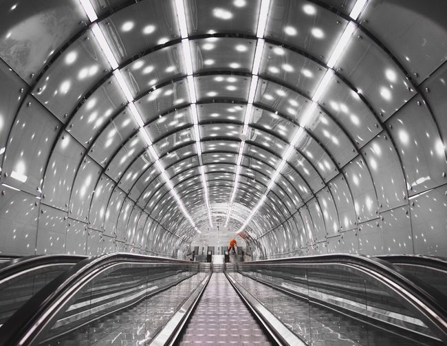 View of escalator in illuminated tunnel