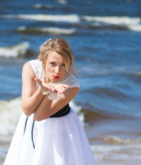 Beautiful woman blowing kiss at beach