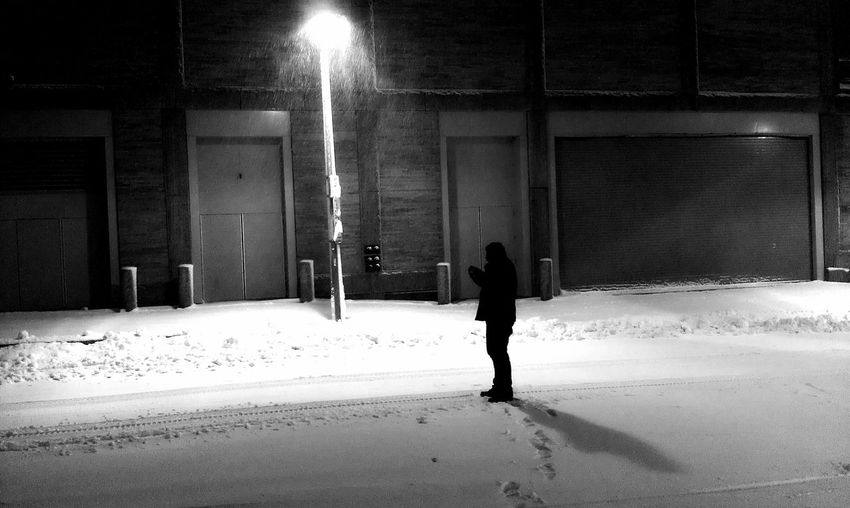 Silhouette Person Standing On Snow Covered Street By Building