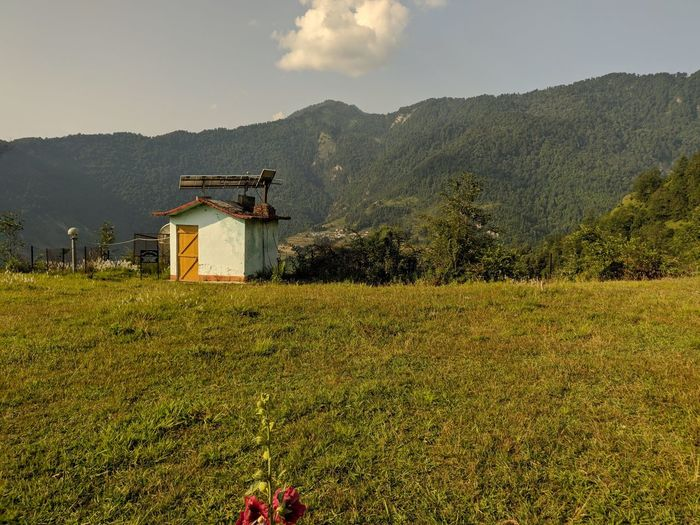 Built structure on field by mountain against sky