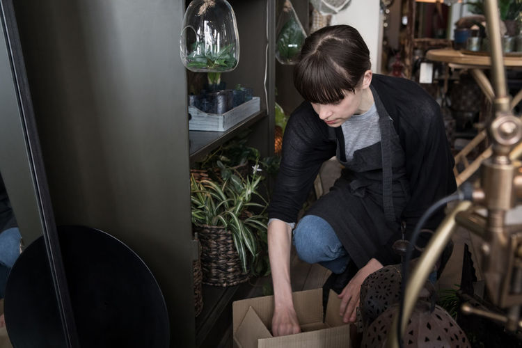 Woman looking at potted plant