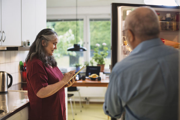 Rear view of woman holding mobile phone at home