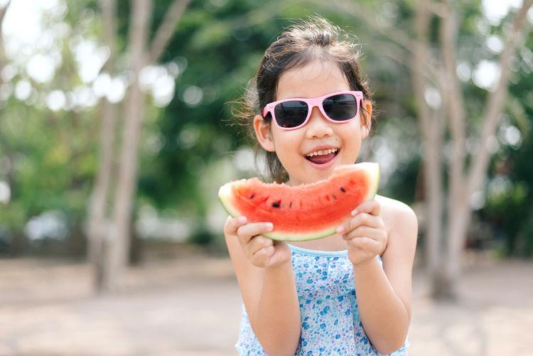 Girl holding watermelon against trees