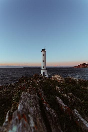 Lighthouse on beach by sea against clear sky