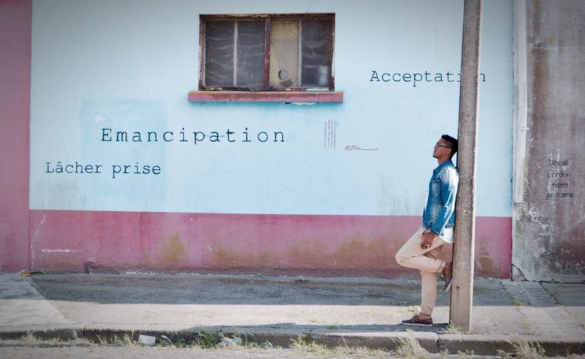 Young man standing by text on wall