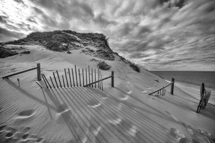 Sand dunes at beach against cloudy sky