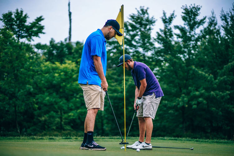 Two Golf Players Practicing Golf Golf Golfing Recreation  Ball Casual Clothing Club Clubs Golf Club Golf Course Golfer Golfers Grass Green - Golf Course Leisure Leisure Activity Lifestyles Outdoors Playing Shot Sport Sports Standing Swing Tree Two People