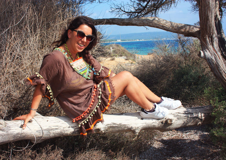 Young caucasian brunette woman on vacation with traditional dress sitting on a tree trunk in ibiza
