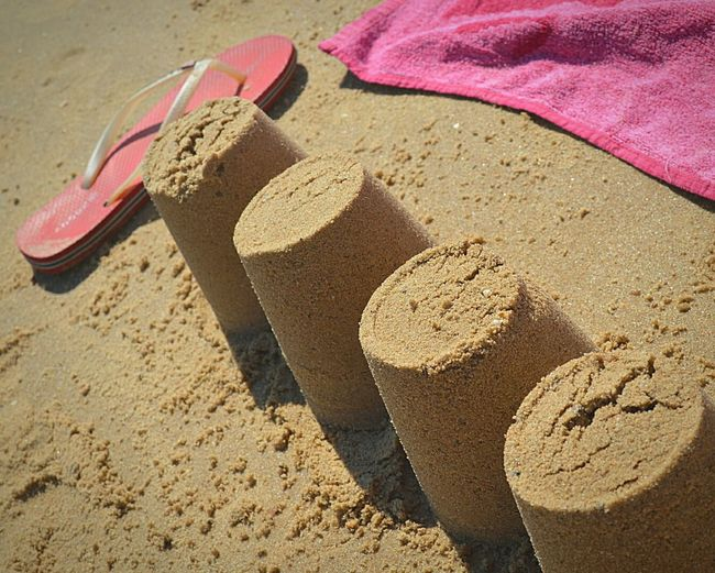 High angle view of sand castles by slipper and blanket at beach