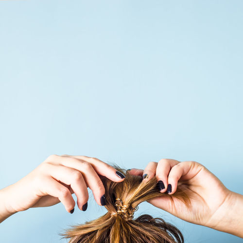 The woman straightens the disheveled bun on her head with her hands with a black manicure. Dark hair is tied with a transparent spiral elastic band. Modern fast hairstyle. Blue background. Copyspace Band Dark Dark Hair Hair Messy Modern Nail Polish Stylish Background Black Blue Bun Finger Hairstyle Human Body Part Human Hand Manicure Messy Hair Straighten Straightening My Hair Transparent Women EyeEmNewHere