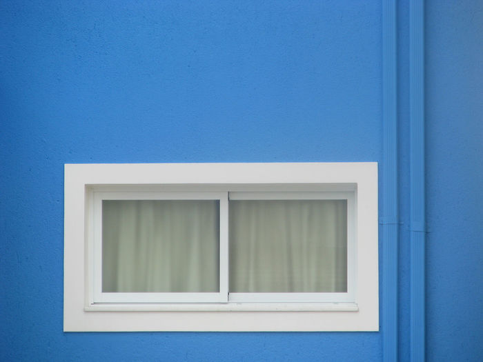 Closed window on blue building