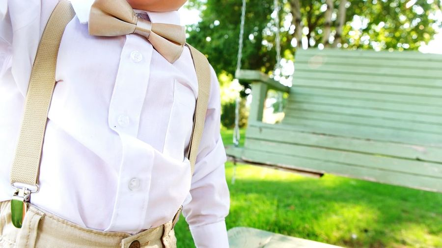 Midsection Of Boy Wearing Bow Tie And Suspenders Standing Against Wooden Bench At Yard