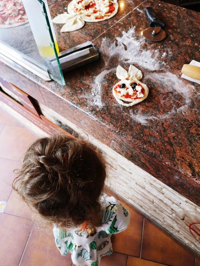 High angle view of young girl whilst food is prepared at restaurant