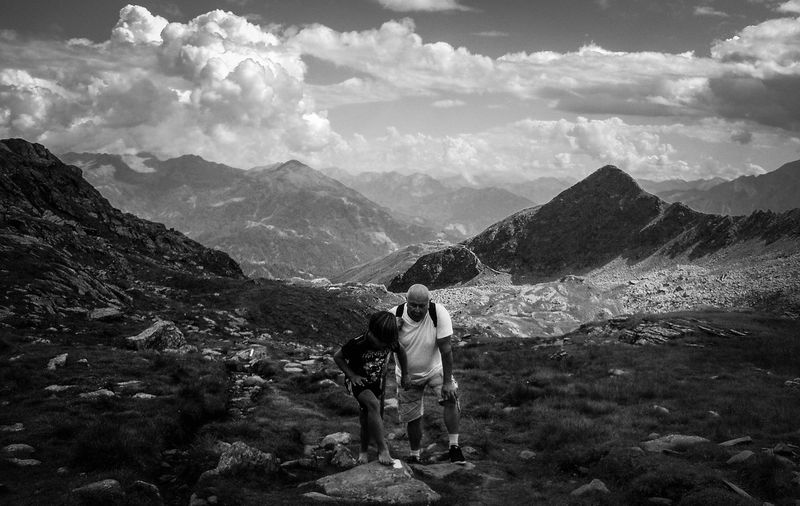 Older man and his grandson standing on mountain against sky