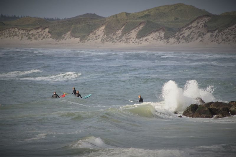 People surfing in sea against mountains