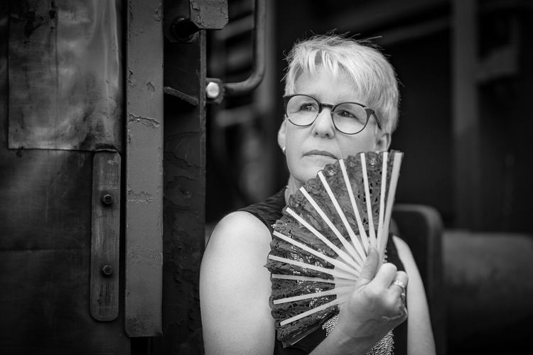 Mature woman holding paper fan