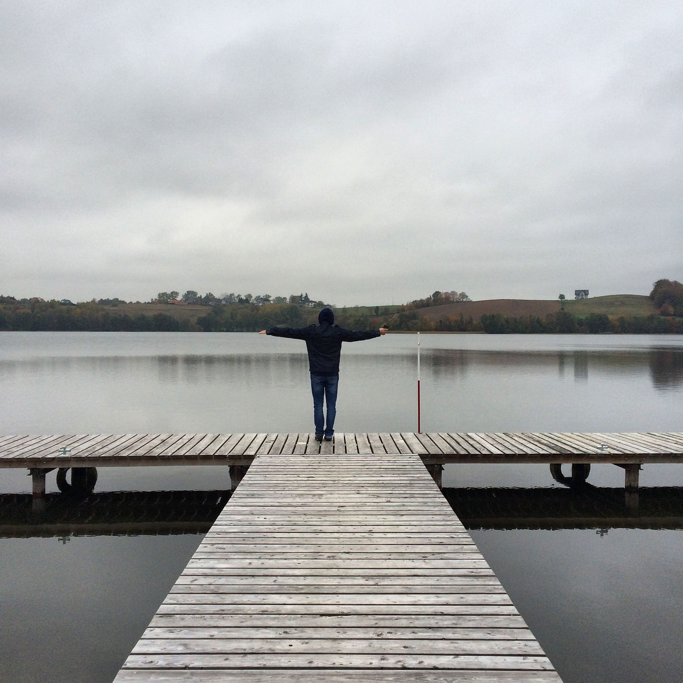 water, rear view, sky, full length, railing, standing, pier, lifestyles, built structure, leisure activity, lake, architecture, river, cloud - sky, tranquility, men, person, casual clothing