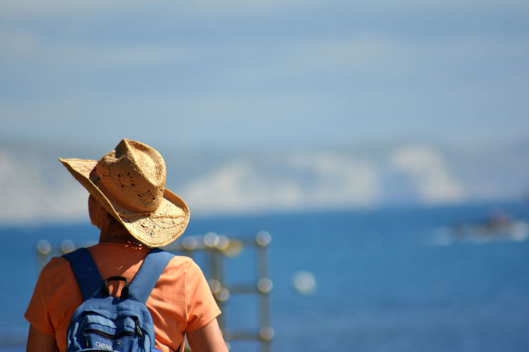 Rear view of woman wearing hat while standing against sea