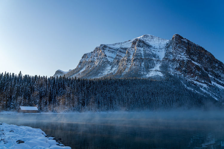 Lake louise boathouse in early winter morning. mist floating on water surface. banff national park.