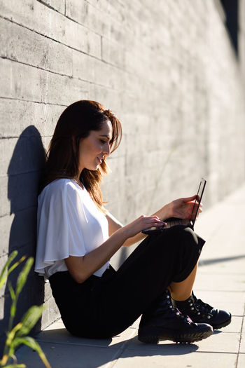 Side view of young woman using laptop while sitting against wall in city