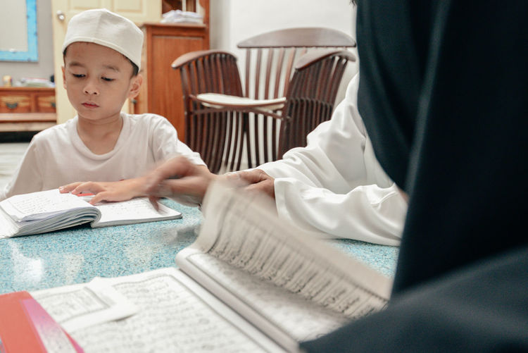 Boy reading koran while sitting at home