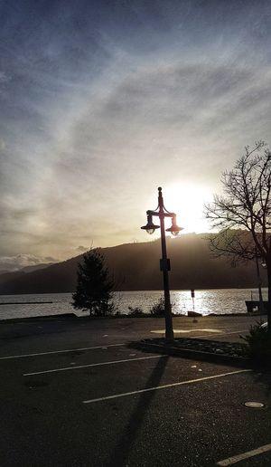 Silhouette cross on street against sky during sunset