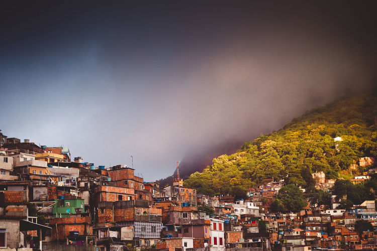 Houses of a slum in city against sky