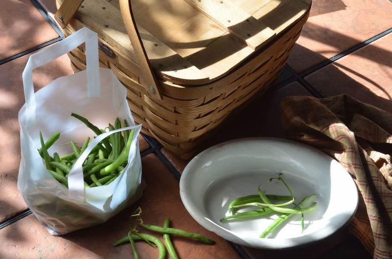 High Angle View Of Green Beans In Bag By Wicker Basket On Table