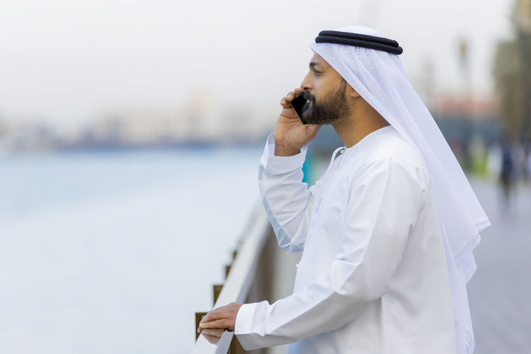 Man in traditional clothing talking over mobile phone while standing outdoors