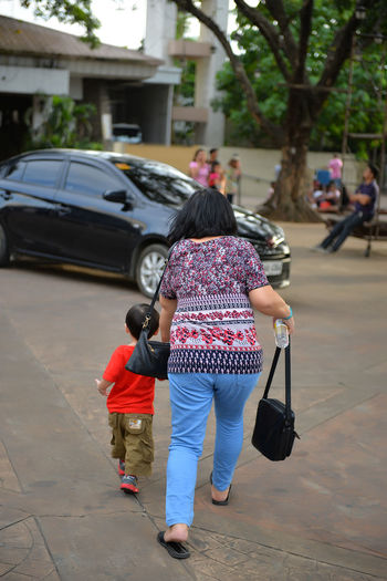 Adult Car Care Child Childhood City Daughter Day Driveway Family Females Full Length Girls Grandmother Mother Offspring Outdoors Packing Parent People Rear View Street Two People Walking Women