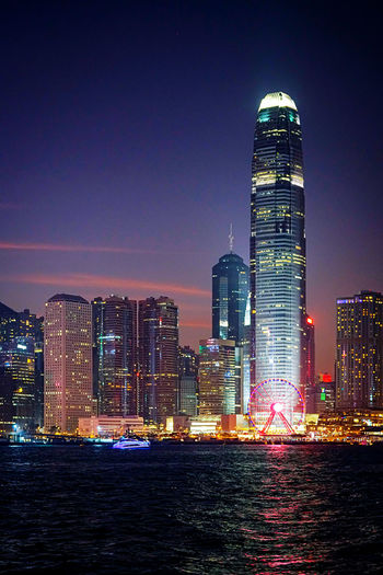Illuminated buildings in city by victoria harbour at night