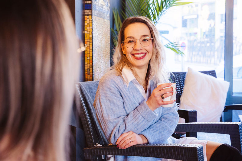 Smiling woman looking at friend while having coffee