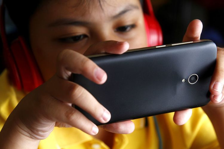 Close-up of boy using phone while listening music against black background