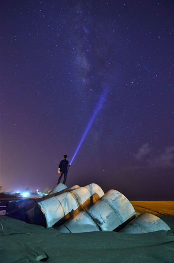 Rear view of man holding illuminated flashlight standing at beach against star field