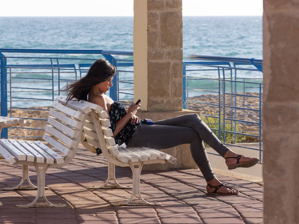 Nahariya, Israel - May 30, 2016: Young girl sits on a sunset on the beach, and wrote a message on a mobile phone in Nahariya, Israel Beach Day Females Girl Israel Lifestyles Message Messaging Mobile Nahariya Nature Phone Ponder Relaxation Sea Sending Sits Sitting Sky Sunlight Sunset Teenager Water Write Young