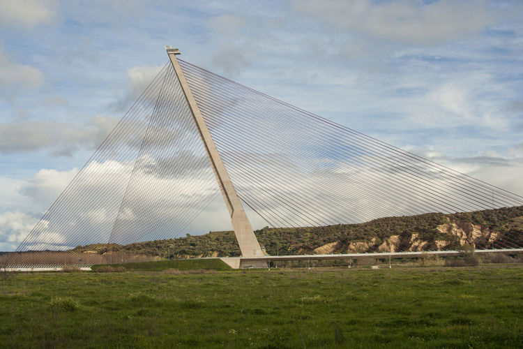 Cable-stayed bridge against cloudy sky