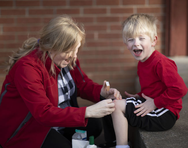 A five-year-old boy, after falling down and scraping his knee, gets medical treatment, love and a bandaid from his mother. Child Childhood Two People Boys Offspring Three Quarter Length Togetherness Smiling Holding Emotion Hair Family Positive Emotion Brick Mouth Open Bandaid Injury Mother Scraped Knee Care Love Maternal Helping Healing Medical