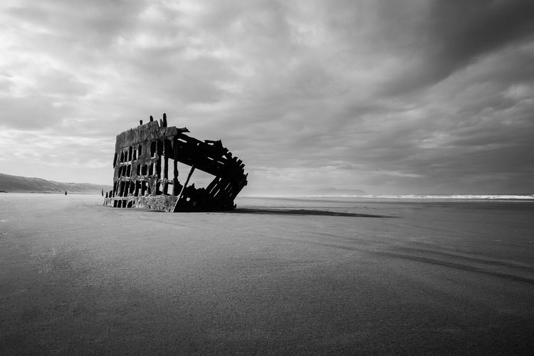 Storm clouds pass overhead the rusted remains of a shipwreck on a beach Architecture Beach Beauty In Nature Black And White Black And White Photography Cloud - Sky Day Fine Art Horizon Over Water Moody Sky Nature No People Outdoors Scenics Sea Shipwreck Shipwreck Beach Sky Tranquil Scene Tranquility Water Wreck